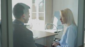 Οι νέοι επαγγελματίες μιλούν καθμένος στο σύγχρονο γραφείο απόθεμα βίντεο