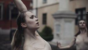 Οι νέοι επαγγελματικοί θηλυκοί χορευτές εκτελούν τον ακροβατικό χορό κατά μήκος της μεσαιωνικής οδού κάτω από τη βροχή κορίτσια υ απόθεμα βίντεο