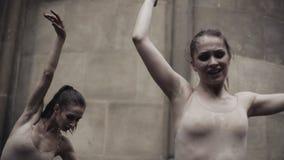 Οι νέοι επαγγελματικοί θηλυκοί χορευτές εκτελούν τον ακροβατικό χορό κατά μήκος της μεσαιωνικής οδού κάτω από τη βροχή κορίτσια υ φιλμ μικρού μήκους