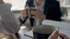 Οι νέοι επιχειρηματίες πίνουν τον καφέ κατά τη διάρκεια της εργάσιμης ημέρας στον πίνακα γραφείων φιλμ μικρού μήκους
