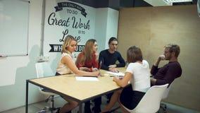 Οι νέοι επιχειρηματίες συζητούν τις νέες στρατηγικές στο ξεκίνημα χρησιμοποιώντας τα lap-top στην αίθουσα συνεδριάσεων των γραφεί απόθεμα βίντεο