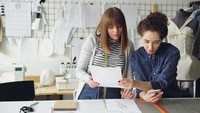 Οι νέοι επιχειρηματίες σχεδίου ιματισμού εξετάζουν τα σκίτσα και ελέγχουν το smartphone Οι ελκυστικές γυναίκες συζητούν απόθεμα βίντεο