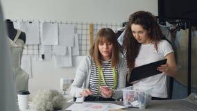 Οι νέοι επιχειρηματίες σχεδίου ιματισμού προσέχουν την ταμπλέτα και επιλέγουν το χρώμα υφάσματος για το ένδυμα στο σκίτσο Ο ράφτη απόθεμα βίντεο