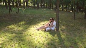 Οι νέοι εραστές εφήβων κάθονται στη χλόη που κλίνει ενάντια σε ένα δέντρο στο πάρκο φιλμ μικρού μήκους