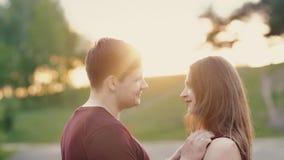 Οι νέοι εραστές στέκονται ο ένας μπροστά από τον άλλον στο ηλιοβασίλεμα Χαμογελούν, ο άνδρας αγγίζει ήπια την τρίχα της, τρίχα κο φιλμ μικρού μήκους
