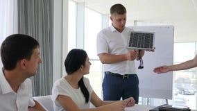 Οι νέοι εργαζόμενοι γραφείων συζητούν τις δυνατότητες και την ηλιακή μπαταρία ανάπτυξης απόθεμα βίντεο