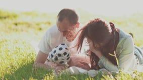 Οι νέοι ευτυχείς γονείς και η λίγο χαριτωμένη κόρη βρίσκονται στην πράσινη χλόη στις φωτεινές ακτίνες του θερινού ήλιου φιλί απόθεμα βίντεο