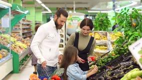 Οι νέοι ευτυχείς γονείς με ένα παιδί αγοράζουν τα λαχανικά στην υπεραγορά απόθεμα βίντεο