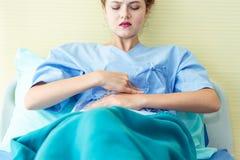 Οι νέοι θηλυκοί υπομονετικοί άρρωστοι με το στομάχι πονούν, εμμηνορροϊκός περίπλοκος, κοιλιακός πόνος περιόδου, τροφική δηλητηρία στοκ εικόνες