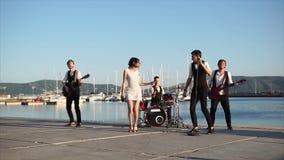Οι νέοι μουσικοί δίνουν μια συναυλία της ζώνης τους στην οδό κοντά στη θάλασσα απόθεμα βίντεο
