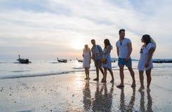 Οι νέοι ομαδοποιούν σχετικά με την παραλία στις θερινές διακοπές ηλιοβασιλέματος, φίλοι περπατώντας την παραλία στοκ φωτογραφία με δικαίωμα ελεύθερης χρήσης