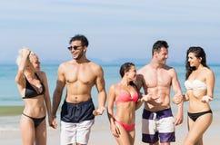 Οι νέοι ομαδοποιούν σχετικά με τις θερινές διακοπές παραλιών, ευτυχείς χαμογελώντας φίλοι που περπατούν τον ωκεανό θάλασσας παραλ Στοκ φωτογραφία με δικαίωμα ελεύθερης χρήσης