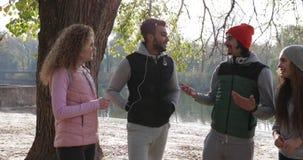 Οι νέοι ομαδοποιούν τη μόνιμη ακτή ποταμών δέντρων υπαίθρια κοντινή, φίλοι που μιλούν το πάρκο φθινοπώρου πρωινού φιλμ μικρού μήκους