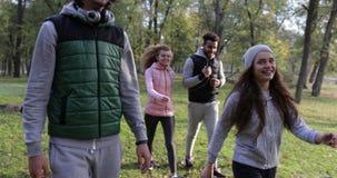 Οι νέοι ομαδοποιούν το περπατώντας ζεύγος δύο υπαίθριο, φίλοι που μιλούν το πάρκο φθινοπώρου πρωινού απόθεμα βίντεο