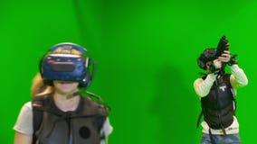 Οι νέοι παίζουν ομαδικά στην εικονική πραγματικότητα σε ένα πράσινο υπόβαθρο VR παιχνίδι σκοπευτών με τη δοκιμή κασκών εικονικής  φιλμ μικρού μήκους