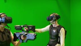 Οι νέοι παίζουν ομαδικά στην εικονική πραγματικότητα σε ένα πράσινο υπόβαθρο VR παιχνίδι σκοπευτών με τη δοκιμή κασκών εικονικής  απόθεμα βίντεο