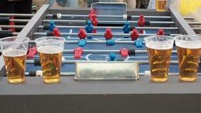 Οι νέοι παίζουν το επιτραπέζιο ποδόσφαιρο και πίνουν την μπύρα υπαίθρια Οι αριθμοί των ποδοσφαιριστών κινούνται αριστερά και σωστ απόθεμα βίντεο