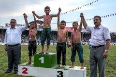 Οι νέοι παλαιστές στέκονται στην εξέδρα νικητών στο τουρκικό φεστιβάλ πάλης πετρελαίου Elmali, Τουρκία Στοκ Εικόνες