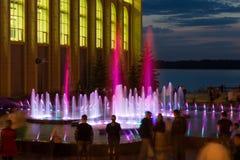 Οι νέοι περπατούν κοντά στην πηγή το βράδυ Στοκ Φωτογραφία