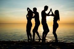 Οι νέοι, σπουδαστές χορεύουν στην παραλία στο ηλιοβασίλεμα backgr στοκ εικόνα