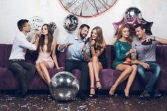 Οι νέοι στηρίζονται ανά τα ζευγάρια σε ένα νυχτερινό κέντρο διασκέδασης Πίνουν τη σαμπάνια και τραγουδούν τα τραγούδια στοκ φωτογραφίες