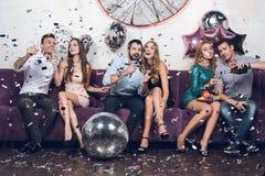 Οι νέοι στηρίζονται ανά τα ζευγάρια σε ένα νυχτερινό κέντρο διασκέδασης Πίνουν τη σαμπάνια και τραγουδούν τα τραγούδια στοκ εικόνα