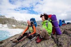 Οι νέοι στηρίζονται στο οδοιπορικό στα βουνά Στοκ Φωτογραφίες