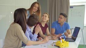 Οι νέοι συζητούν κάτι στο lap-top στο γραφείο στοκ φωτογραφία