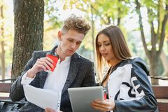 Οι νέοι συνέταιροι κοιτάζουν μέσω των εγγράφων τους και κάθονται σε έναν πάγκο στην οδό στοκ εικόνα με δικαίωμα ελεύθερης χρήσης