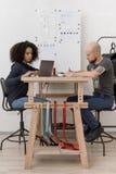 Οι νέοι σχεδιαστές εργάζονται στον πίνακα Στοκ Εικόνες