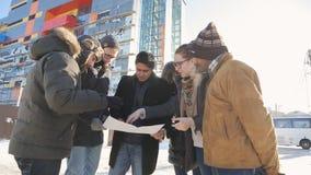 Οι νέοι σχεδιαστές στέκονται στην οδό και συζητούν το σχέδιο της κατασκευής φιλμ μικρού μήκους