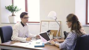 Οι νέοι υπάλληλοι εργάζονται και μιλούν στην κορυφαία επιχείρηση φιλμ μικρού μήκους