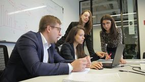 Οι νέοι υπάλληλοι εργάζονται στο γραφείο με το lap-top στη μεγάλη επιχείρηση απόθεμα βίντεο