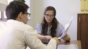 Οι νέοι υπάλληλοι συζητούν τα έγγραφα εργασίας καθμένος στην επιχείρηση απόθεμα βίντεο
