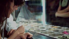 Οι νέοι φίλοι ήρθαν στην περίπτωση επίδειξης γυαλιού vitrine με τα συστατικά για τα πιάτα και επιλέγουν τι θέλουν φιλμ μικρού μήκους