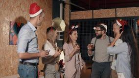 Οι νέοι φίλοι κουβεντιάζουν και πίνουν στη γιορτή Χριστουγέννων απόθεμα βίντεο