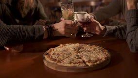 Οι νέοι χτυπούν τα γυαλιά πέρα από το πιάτο με την πίτσα στον καφέ, κινηματογράφηση σε πρώτο πλάνο απόθεμα βίντεο