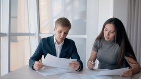 Οι νέοι όμορφοι επιχειρηματίες εργάζονται μαζί, καθμένος στο σύγχρονο γραφείο φιλμ μικρού μήκους