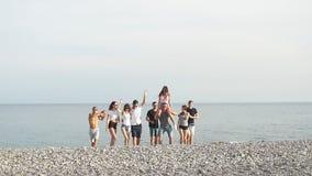 Οι νεαροί άνδρες που δίνουν τις φίλες τους piggyback η παραλία γύρων απόθεμα βίντεο