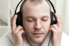 Οι νεαροί άνδρες ακούνε μουσική στα ακουστικά Στοκ φωτογραφίες με δικαίωμα ελεύθερης χρήσης