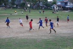 Οι νεαροί άνδρες παίζουν το ποδόσφαιρο στο Νεπάλ Στοκ Φωτογραφίες
