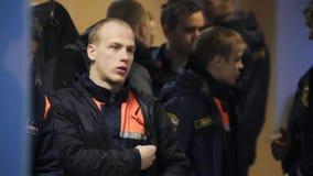 Οι νεαροί άνδρες στα πορτοκαλιά σακάκια emercom περιμένουν στη γραμμή στην αίθουσα ομάδα απόθεμα βίντεο