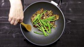 Οι νεαροί βλαστοί σκόρδου και τα τεμαχισμένα κομμάτια των μανιταριών με τη λωρίδα κοτόπουλου είναι τηγανισμένοι στο πετρέλαιο σε  απόθεμα βίντεο