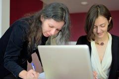 Οι νεολαίες έντυσαν επιδέξια την κυρία βοηθούν μια άλλη νέα κυρία για να εργαστούν με τα έγγραφα, να γεμίσουν τις μορφές και το σ στοκ εικόνα με δικαίωμα ελεύθερης χρήσης