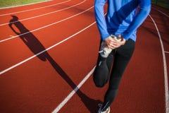 οι νεολαίες γυναικών τεντώματος τρεξίματός της Στοκ εικόνα με δικαίωμα ελεύθερης χρήσης