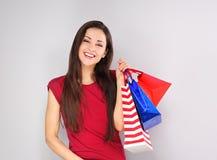 Οι νεολαίες διέγειραν την οδοντωτή χαμογελώντας γυναίκα με τις τσάντες αγορών Διακοπές καλής χρονιάς γυναίκα πορτρέτου προσώπου κ στοκ φωτογραφία με δικαίωμα ελεύθερης χρήσης