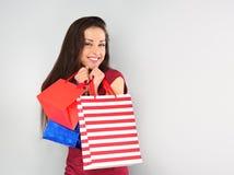 Οι νεολαίες διέγειραν την οδοντωτή χαμογελώντας γυναίκα με τις τσάντες αγορών στις διακοπές καλής χρονιάς στο μπλε υπόβαθρο στοκ εικόνα με δικαίωμα ελεύθερης χρήσης