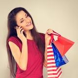 Οι νεολαίες διέγειραν την οδοντωτή χαμογελώντας γυναίκα με τις τσάντες αγορών που μιλούν στο κινητό τηλέφωνο και που ανατρέχουν Δ στοκ εικόνα με δικαίωμα ελεύθερης χρήσης