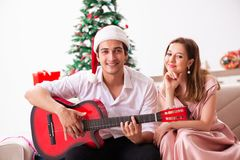 Οι νεολαίες συνδέουν την κιθάρα παιχνιδιού στα Χριστούγεννα στοκ εικόνες