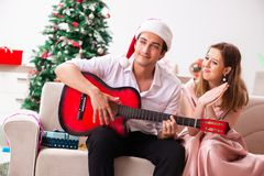 Οι νεολαίες συνδέουν την κιθάρα παιχνιδιού στα Χριστούγεννα στοκ φωτογραφίες